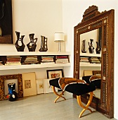 Upholstered stool against full-length mirror with wooden frame and ethnic vases in masonry shelving