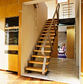 Staircase in open foyer with view into living room