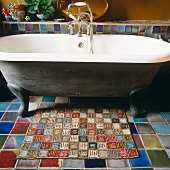 Vintage bathtub on multi-coloured floor tiles