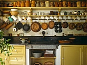 Cups and baskets hanging from kitchen shelf above rustic kitchen counter