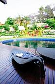 Designer lounger on wooden deck next to round pool