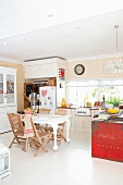 Dining area with antique table and modern garden chairs in open-plan kitchen