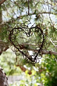 A wire heart hanging in a tree