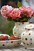 Bouquet of roses and strawberries on garden table