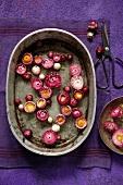 Rosarote Gartenstrohblumen, schwimmend in einer alten Zinkschale auf violetter Leinenserviette