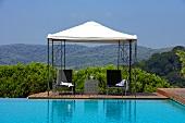 Stühle und Tisch unter der Pergola am Infinity-Pool mit Blick auf Berglandschaft