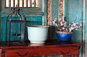 Flowering twigs in blue pot and lantern on antique console table against painted and carved wooden wall