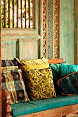 Cushions on wooden bench in front of painted and carved wooden wall