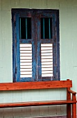 Mahogany bench against outside wall below window with closed wooden shutters