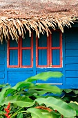 Blue-painted wooden hut with closed shutters and thatched roof