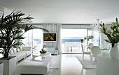 Moderner Wohnraum in Weiss mit Loungebereich und Essplatz in Weiss in zeitgenössischer Architektur mit Terrasse und Meerblick