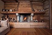 Offener Kamin an holzverkleideter Wand mit rustikalem Holzbalken als Kaminsims; neben dem Kamin gestapeltes Brennholz und Dekobäume aus rostigem Eisen
