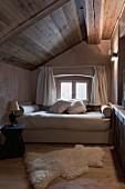 Einfaches, gemütliches Schlafzimmer unter der Dachschräge mit kleinem Fenster; am Boden ein weicher Fellteppich