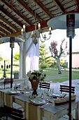 Festively set table on roofed terrace with patio heater and view of garden