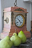 Green pears in front of antique clock on shelf