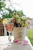 Refreshing drink and bouquet in metal bucket on table
