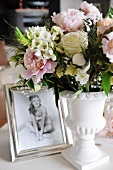 Festive bouquet in white china vase next to framed photo
