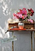 Bouquet on rusty, vintage garden table against exterior wall