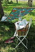 Crockery and picnic basket on chair in front of hammock hanging in garden