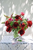Flamboyant summer bouquet on table with pattern of light and shade on exterior wall