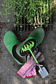 Still-life with gardening tool and gloves next to gardening clogs