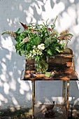 Hand-picked bouquet on rusty garden table against exterior wall