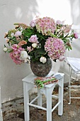 Bouquet of hydrangeas in vase on white-painted stool against exterior wall