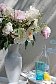 Summer bouquet in white ceramic vase next to retro-style drinking glass and bottle on garden chair