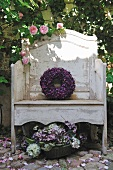 Wreath of violet flowers on weathered garden bench and bowl of flowers on cobbled floor