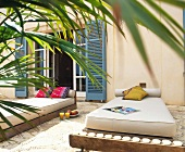 Designer outdoor couches with light cushions in front of house