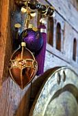 Ein kupferfarbener Anhänger, Kugel und Quaste in Violett als exotischer Weihnachtsschmuck an geschmiedeter Türklinke