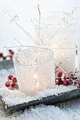 Brennendes Windlicht in Gläsern mit Kunstschnee verziert und rote Ilexbeeren auf Schale