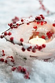 Ice tealight holder with winterberries and candle in artificial snow