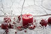 Rote Kerze mit Ilexbeeren im Kunstschnee