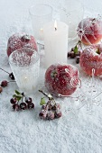Pomegranates, apples and berries next to lit candles on surface covered in artificial spray snow