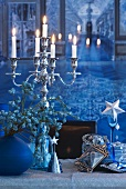 Lit candles in candlestick and Christmas decorations on table top