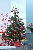 Heaps of presents under Christmas tree with red decorations