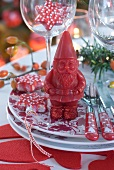 Red and white Christmas place setting with Father Christmas candle
