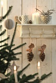 Wooden pine cones with moose heads hanging from coat rack with crockery and candles on shelf above
