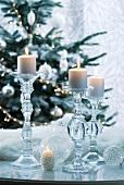 Kerzenhalter aus Glas mit brennenden Kerzen vor Tannenbaum