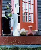 Auf die Terrasse gestellte Schuhe und Stiefel und Stiefelvase mit Apfelzweig warten auf den Nikolaus