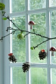 Branch in front of window decorated with pine cones and fly agaric ornaments