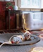 Holzteller mit Eselfigur aus Gips, Lichterkette, Äpfeln und Nüssen auf Teppich