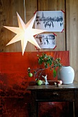 Star-shaped lantern in front of black and white postcards on wooden wall and above twigs on side table
