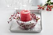 Rote Kerze in einer Eisschale mit Johanniskraut- und Skimmia-Japonica-Beeren und Kunstschnee