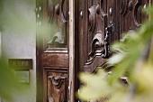 Holzgeschnitzte Eingangstür und moderne Türklingel in Hauswand