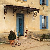 Pretty metal porch and blue-painted wooden elements combined with ochre-coloured facade of old, French country house