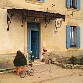 Verspieltes Metallvordach und blau gestrichene Holzelemente zur ockerfarbenen Fassade eines alten, französischen Landhauses