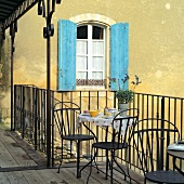 Metal bistro table set for two on wooden balcony with simple metal railing; blue shutters in background