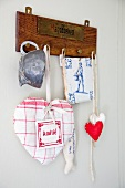 Fabric love hearts, tile coaster and old cup hanging from wooden peg board
